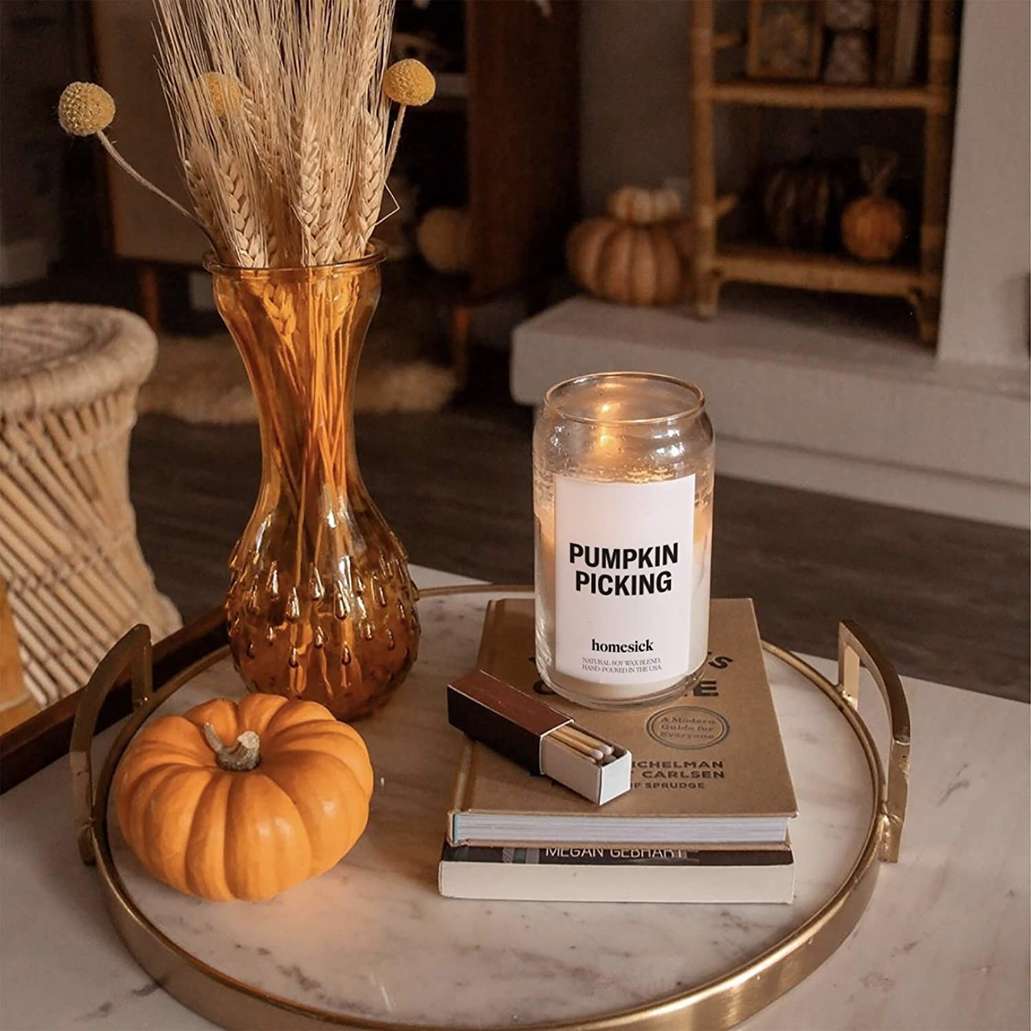 """a candle with a label on it that says """"pumpkin picking"""" near other fall decor"""
