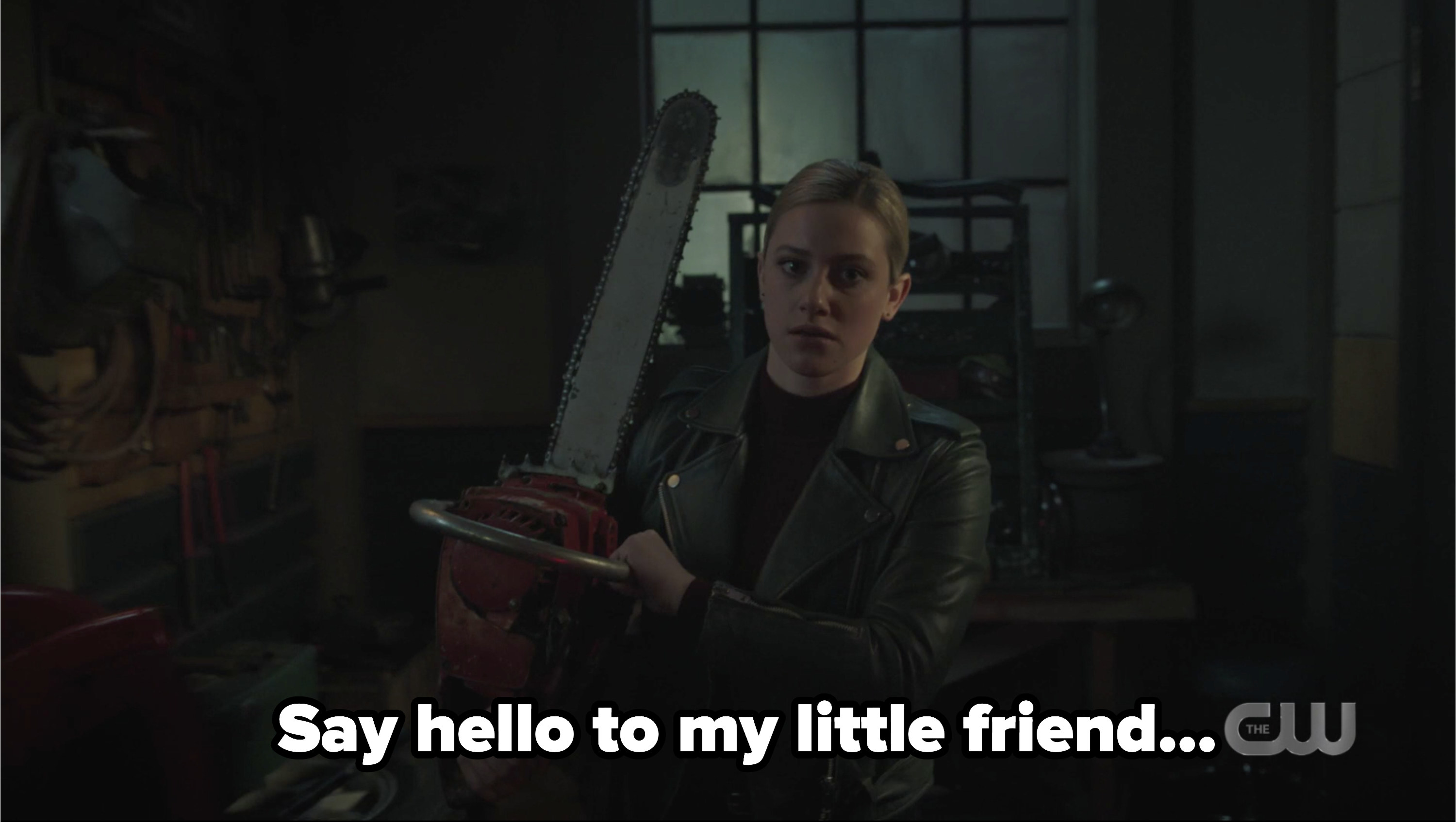 Betty holding a chainsaw with the caption say hello to my little friend
