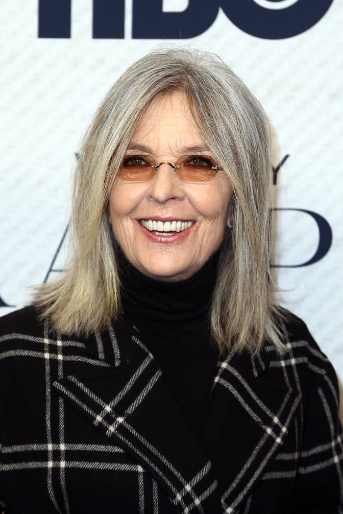 Diane Keaton, wearing a checkered coat and dark turtleneck, smiling at a red carpet event