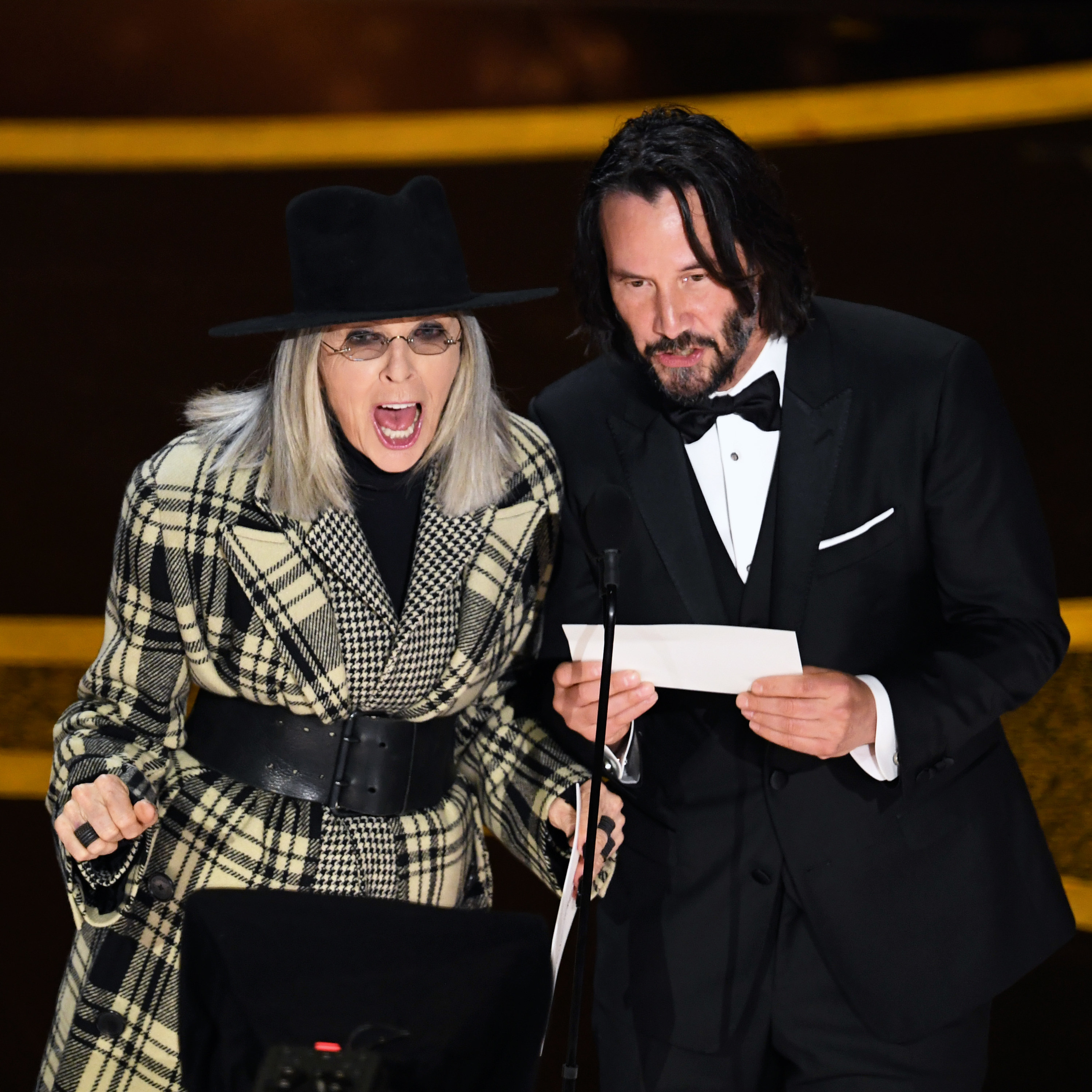 Diana and Keanu Reeves presenting an award on stage
