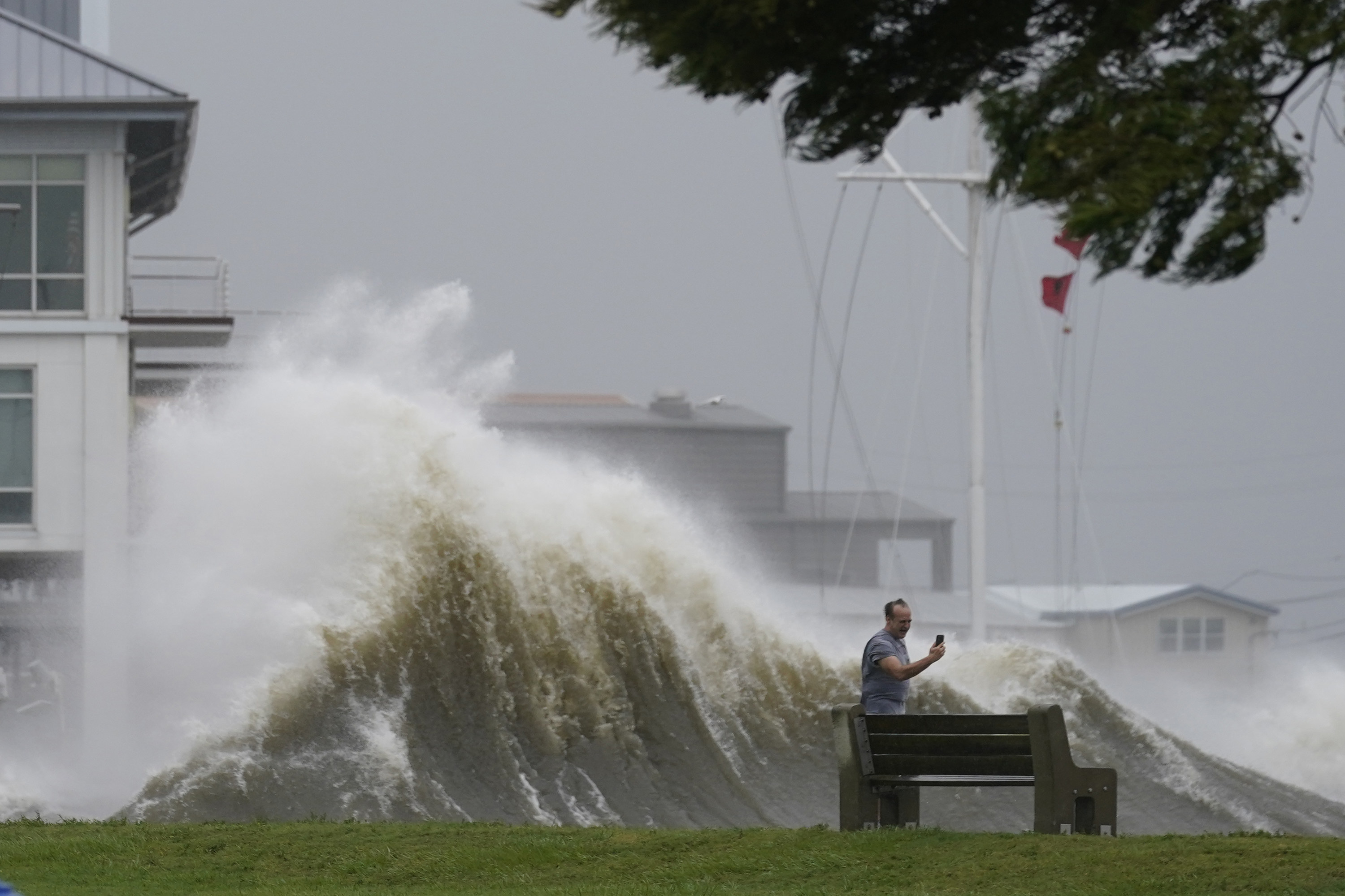 A man takes a selfie with a massive storm well wave behind him