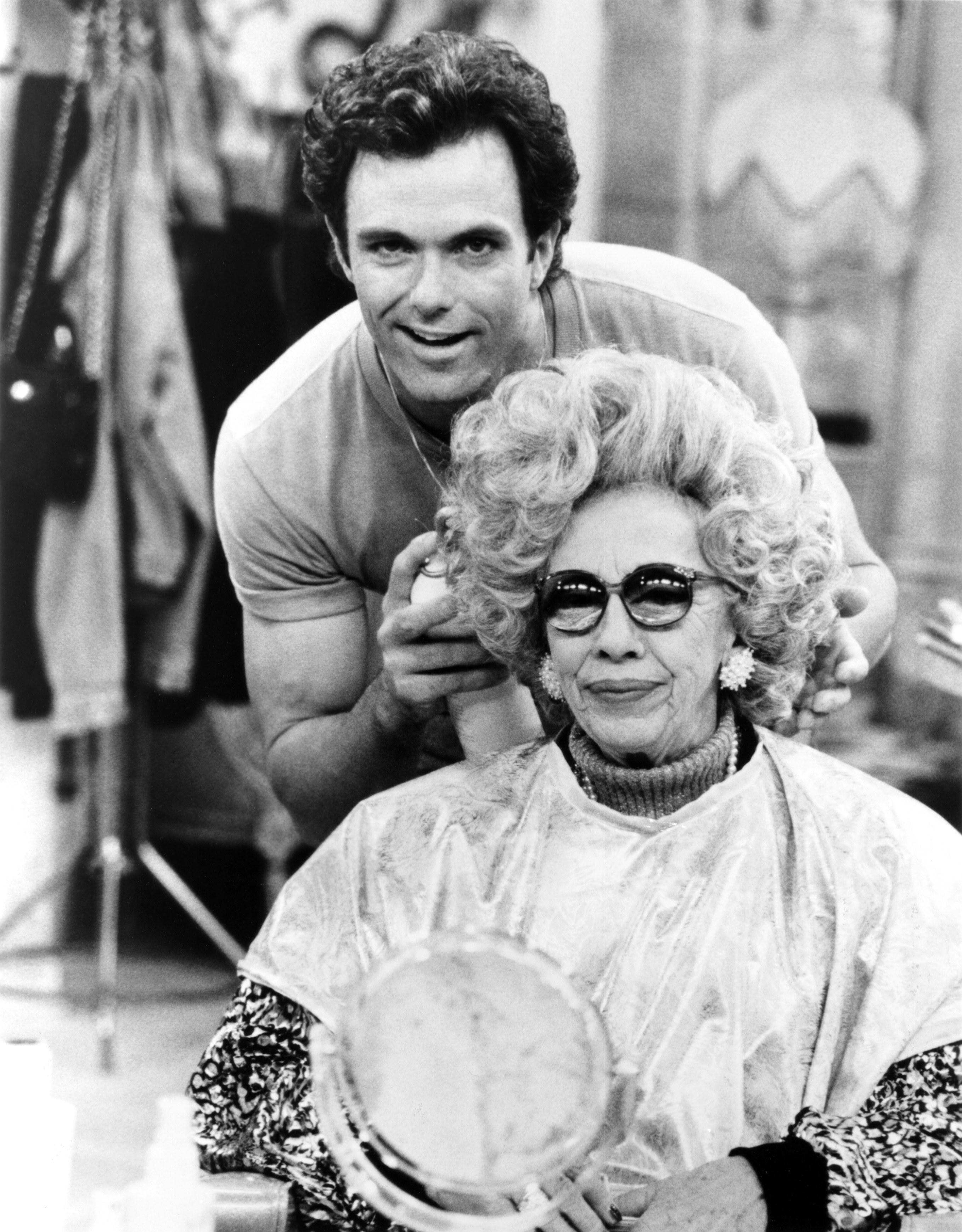 Man doing a woman's hair at a salon