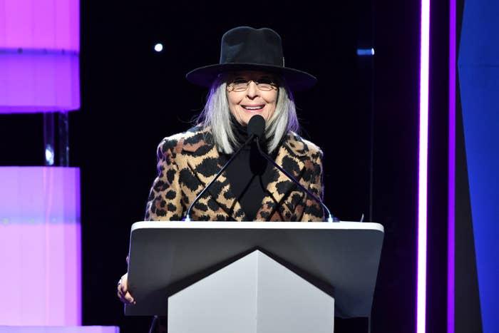 Diane speaking at a podium in an animal-print jacket, turtleneck, and fedora