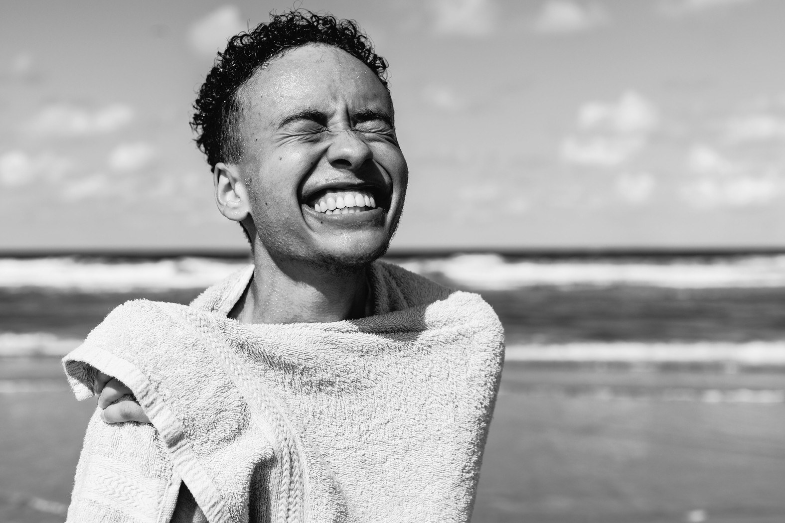 A young person smiles wide at the camera while wrapped in a towel, the ocean in the background