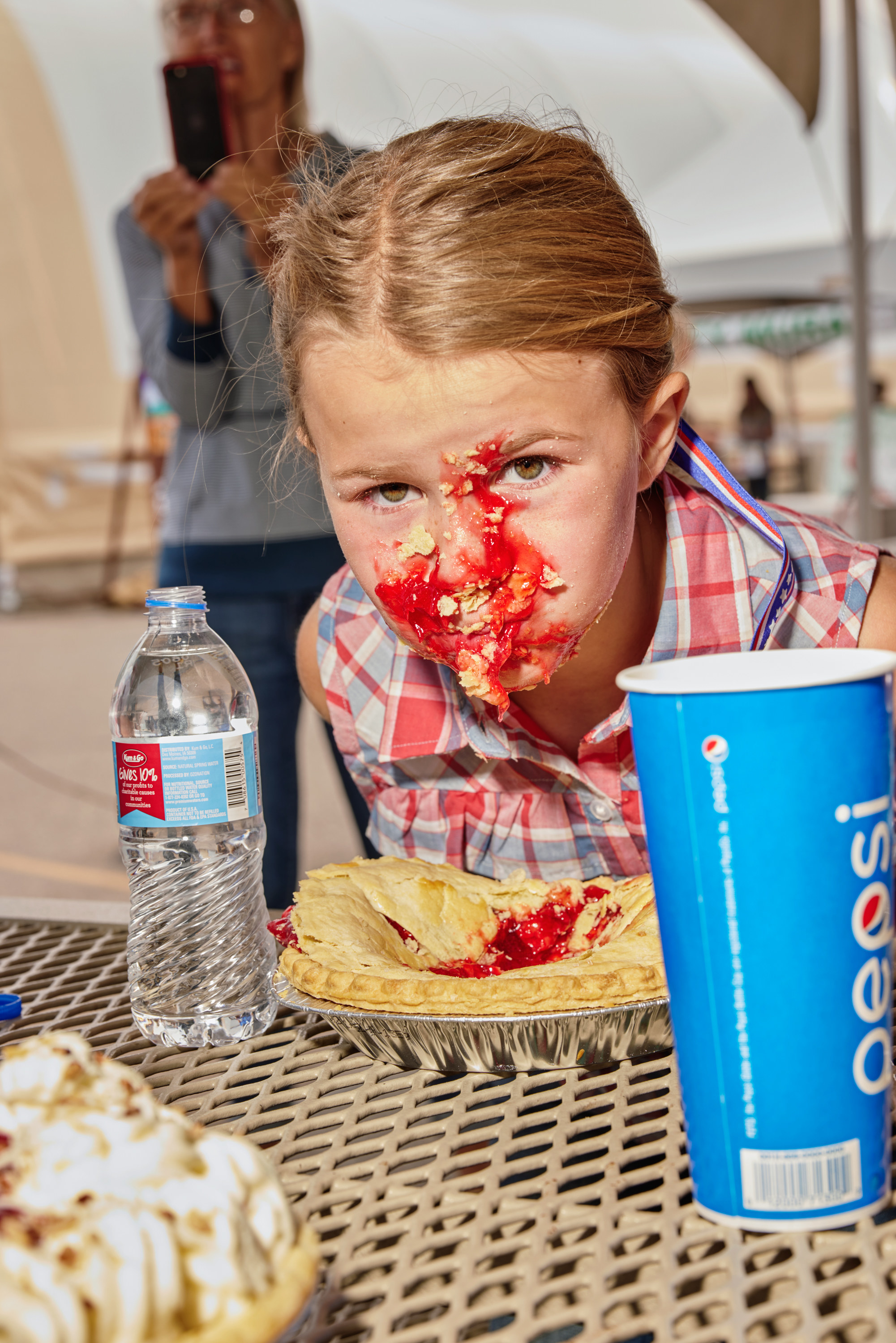 A girl lifts her face up from a pie, with pie filling all over her face, and a bottle of water to her left
