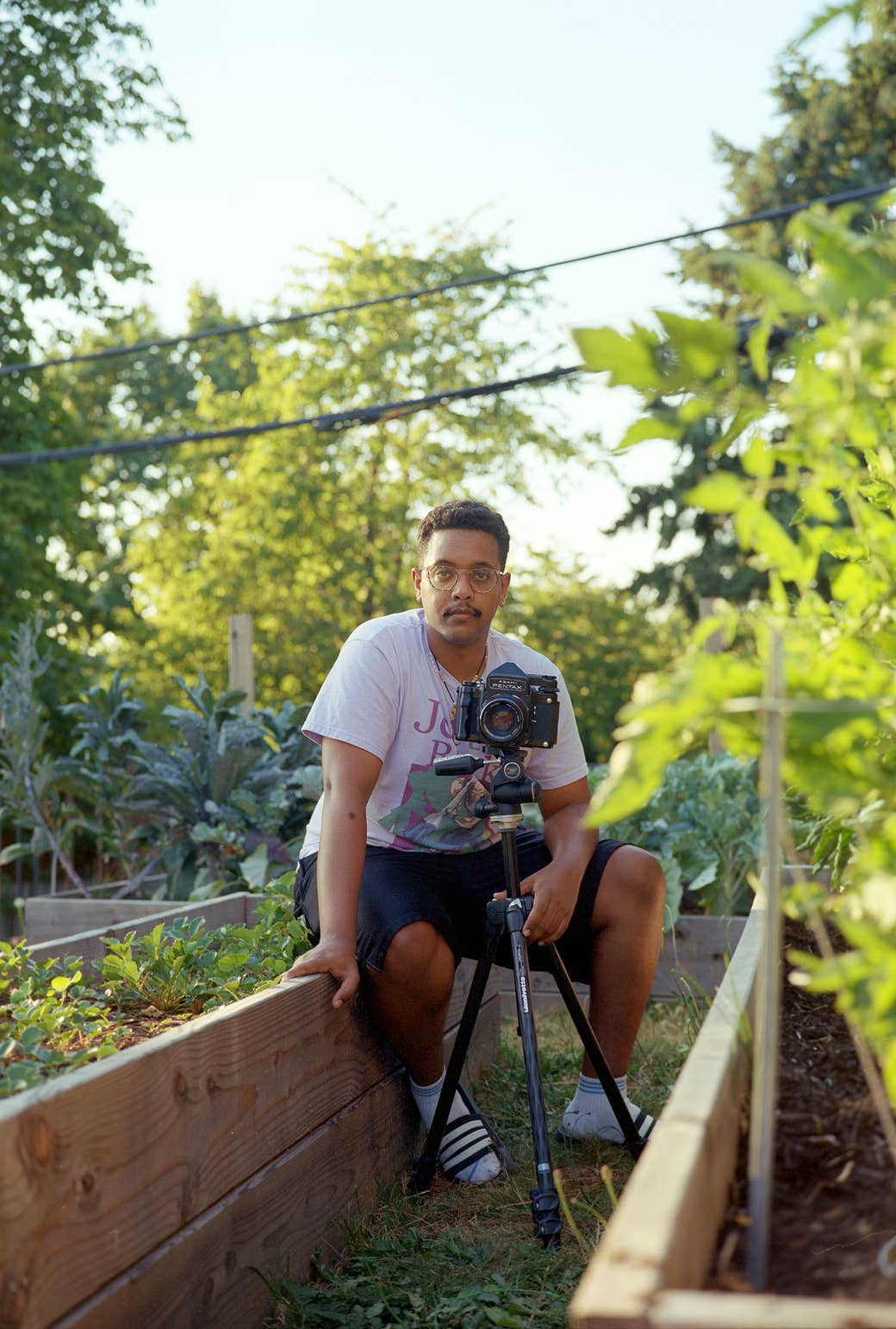 The photographer sits in his garden with a medium format camera, facing the camera
