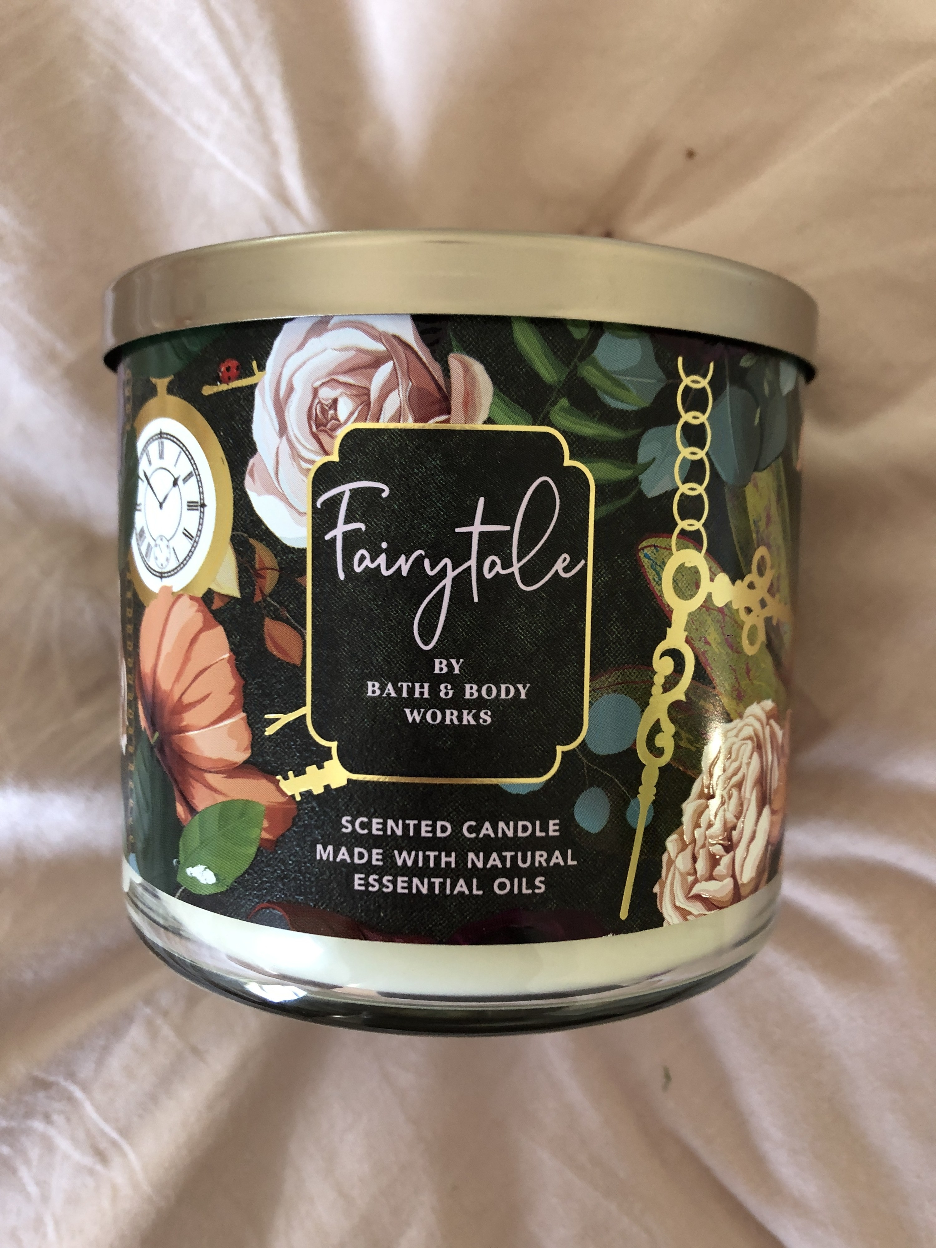 """bath and body work's """"fairytale"""" candle with florals around the label"""