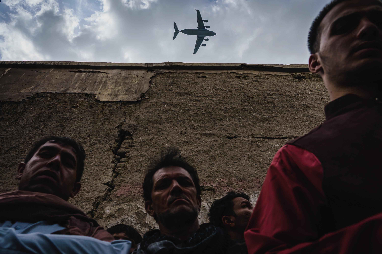 Three Afghan men stand against a wall, a plane flies overhead