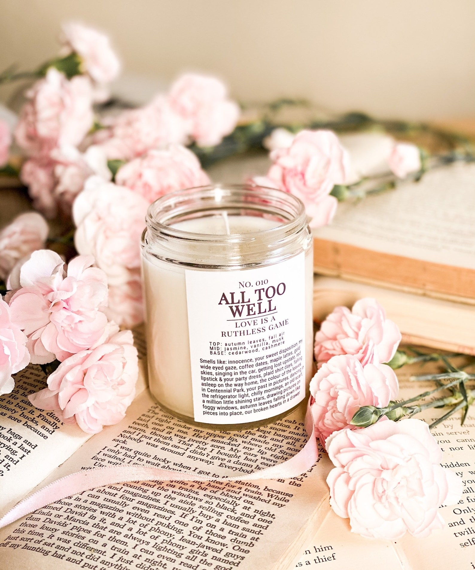 """a white candle with a label on that says """"all too well love is a ruthless game"""" and a paragraph under it as well"""
