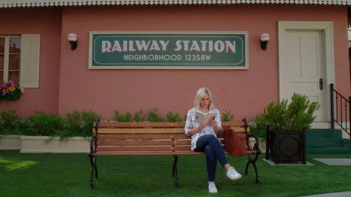 Eleanor sitting beneath a sing that says, Railway Station, neighborhood 12358W