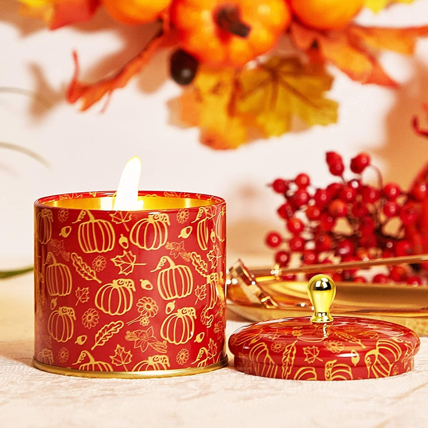 a candle in an orange jar with gold outlines of pumpkins and leaves