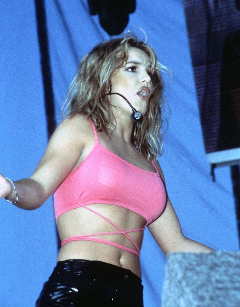 Britney performing in a pink sports bra inspired top