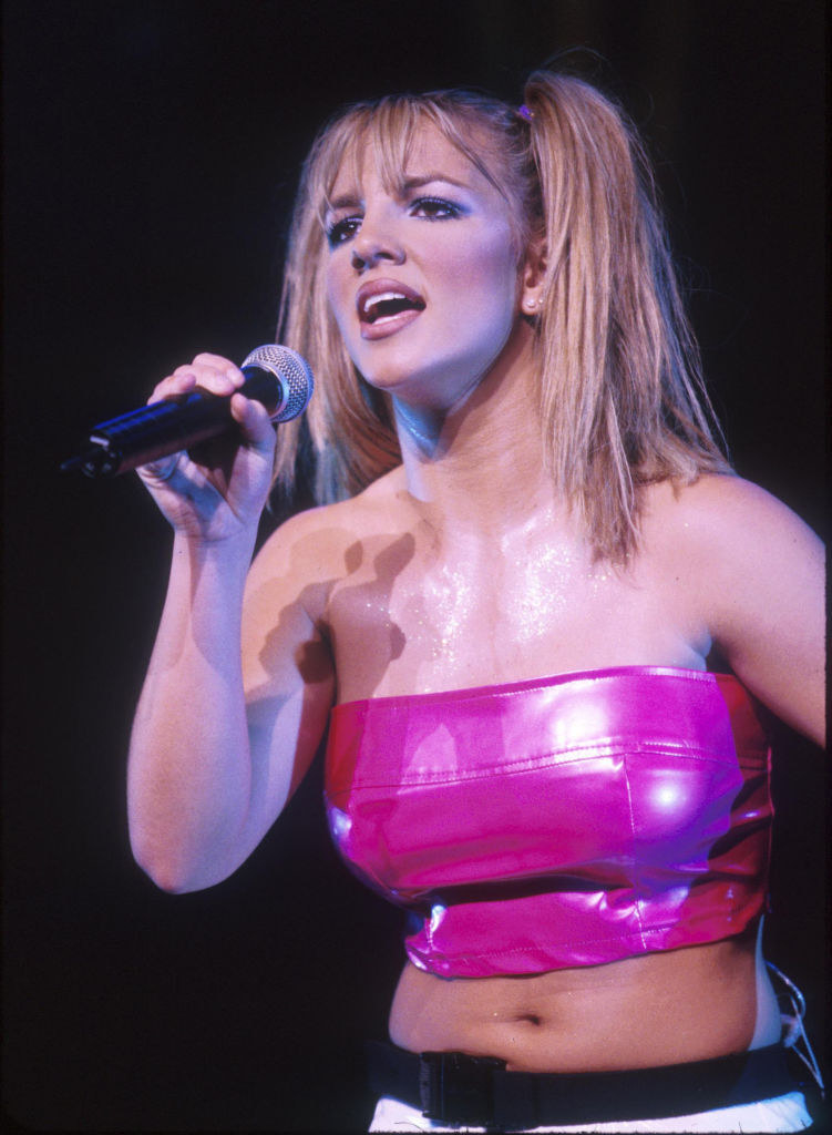 Photo of Britney performing in a pink crop top and pigtails