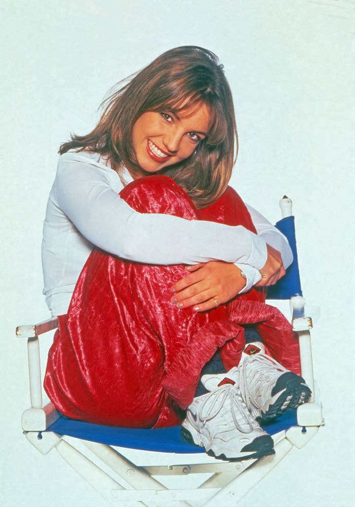 Photo of Britney posing in red pants and a white long sleeved top