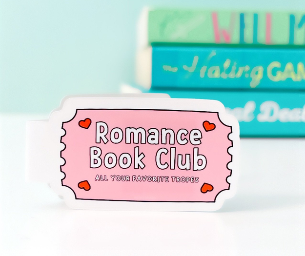 """A white magnetic bookmark with a pink graphic shaped like a ticket that says """"Romance Book Club, All Your Favorite Tropes"""""""
