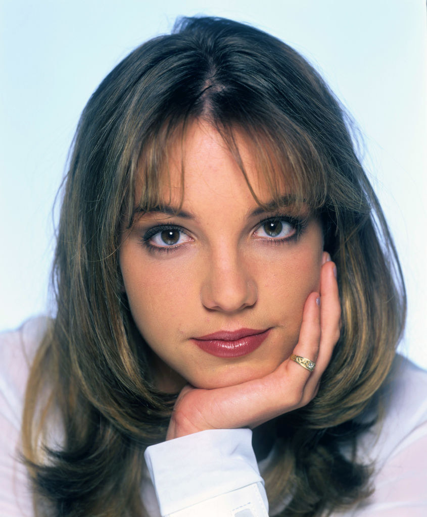 Close up photo of Britney with bangs and layers posing for a photo