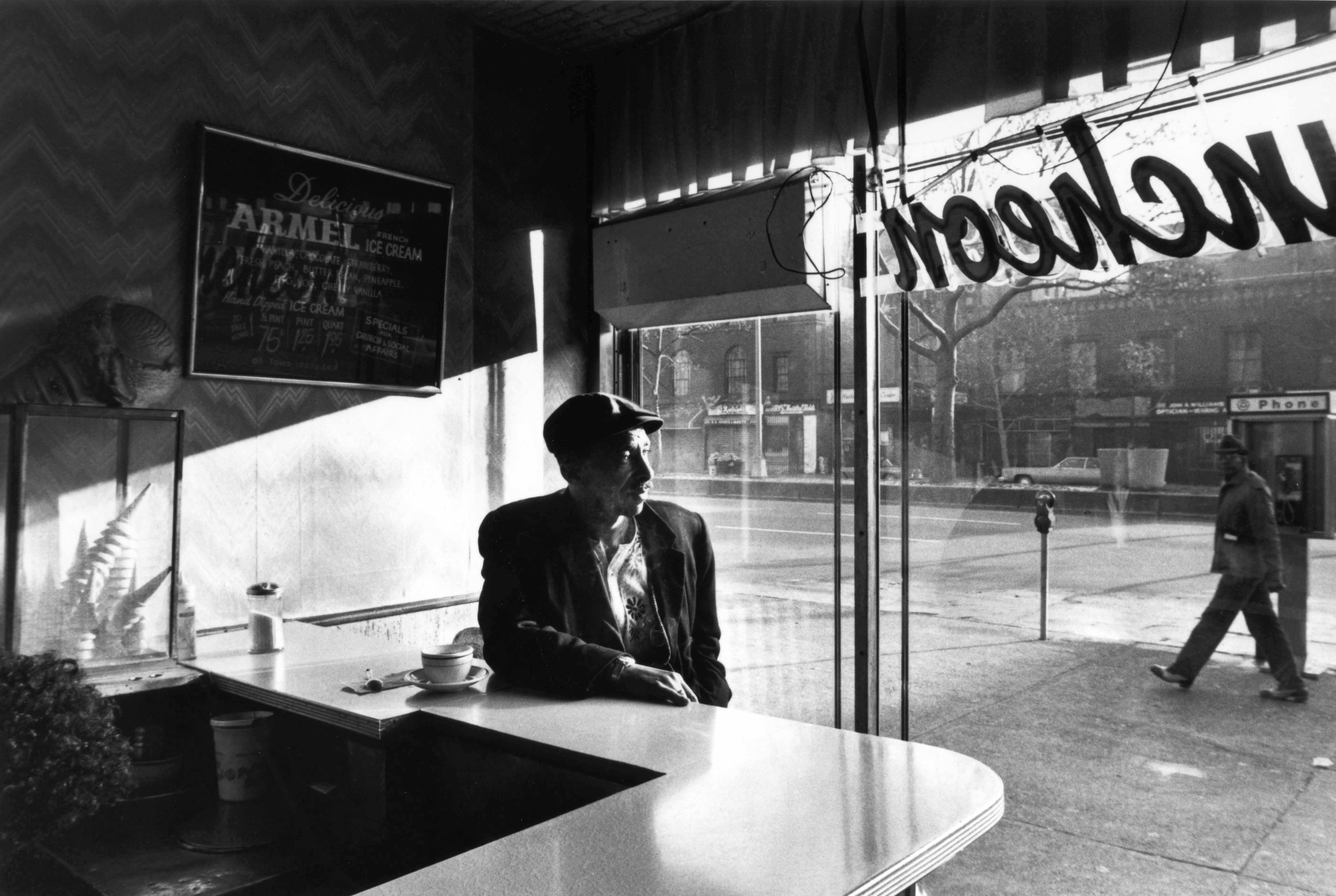 A man sits at a diner counter alone with a cup of coffee, looking out the window as another man walks by