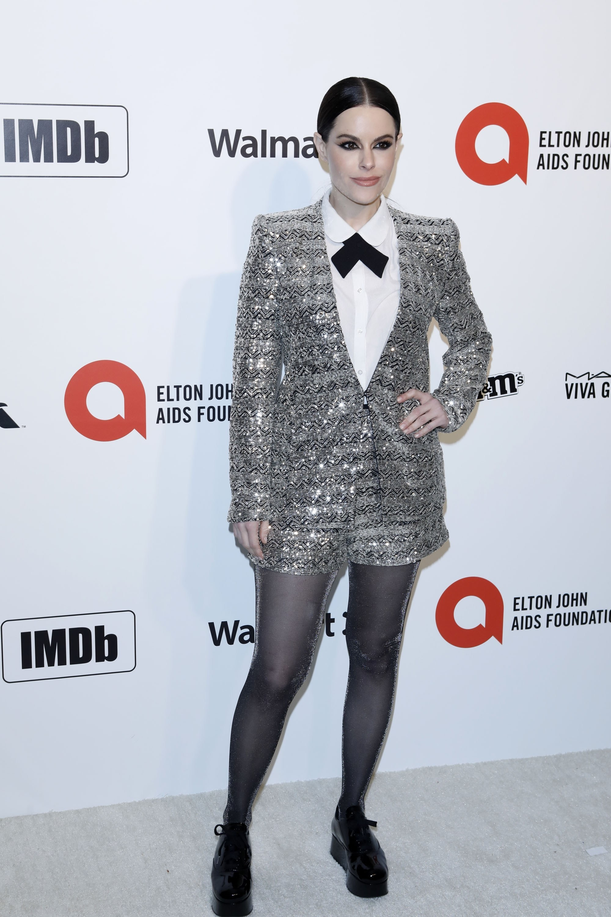 Emily Hampshire wears a tuxedo dress at a red carpet event