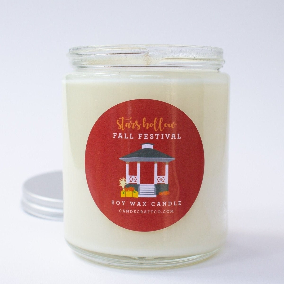 a white candle with the stars hollow gazebo on it in a red circle