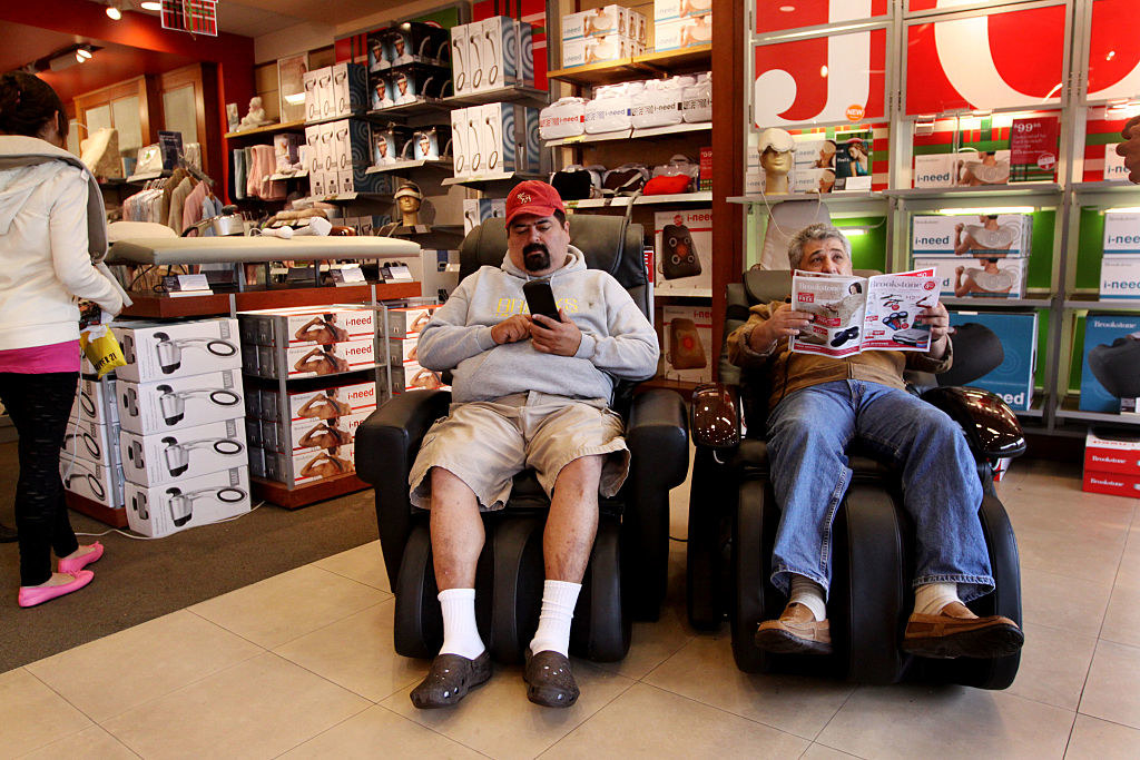 Two dads recline on massage chairs in a Brookstone
