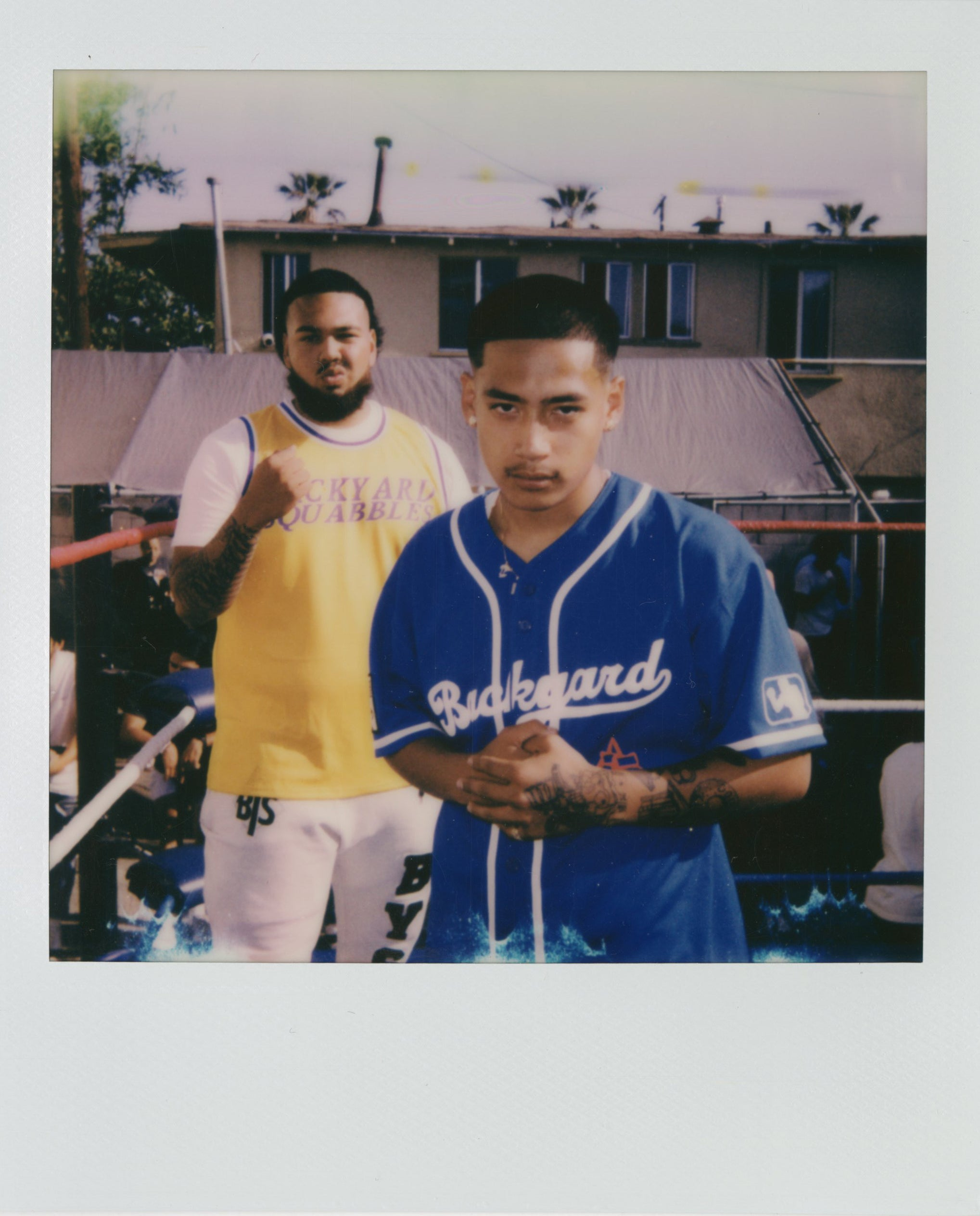 A polaroid picture of two men in backyard squabble gear standing in an outdoor boxing ring