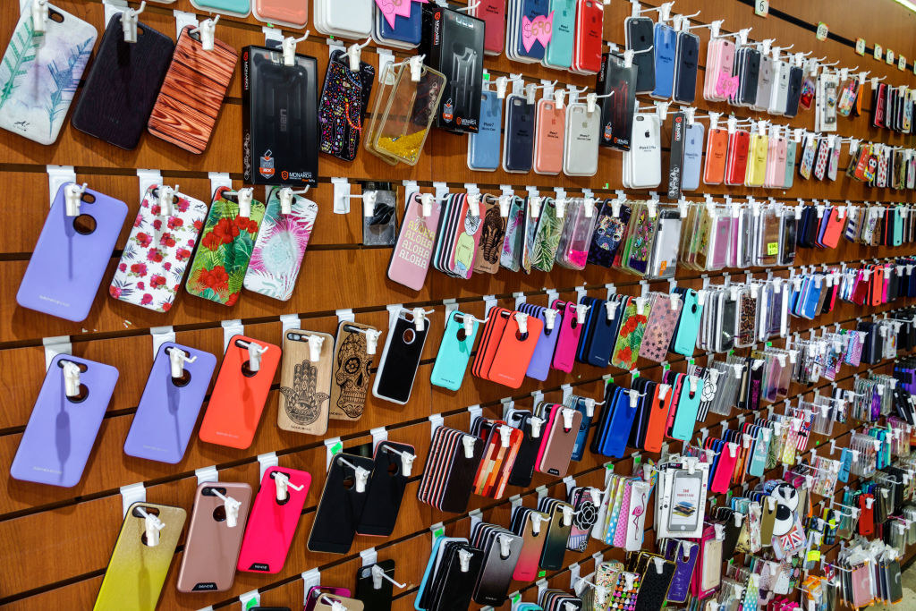 A bunch of smart phone covers hanging on the wall