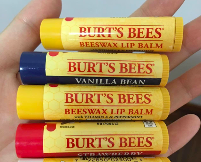reviewer's hand holding five lip balms in different flavors