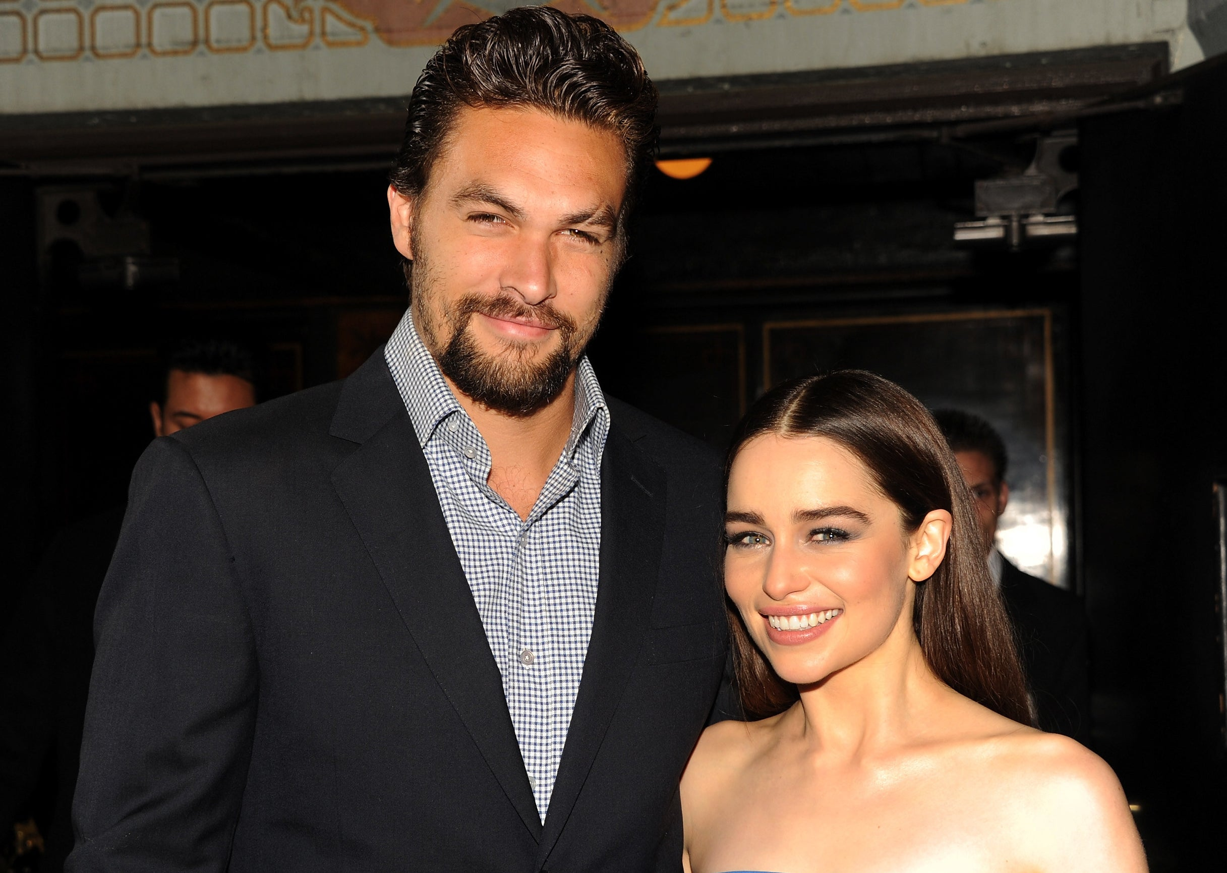 Jason looks formal in a check shirt and blazer while posing next to Emilia