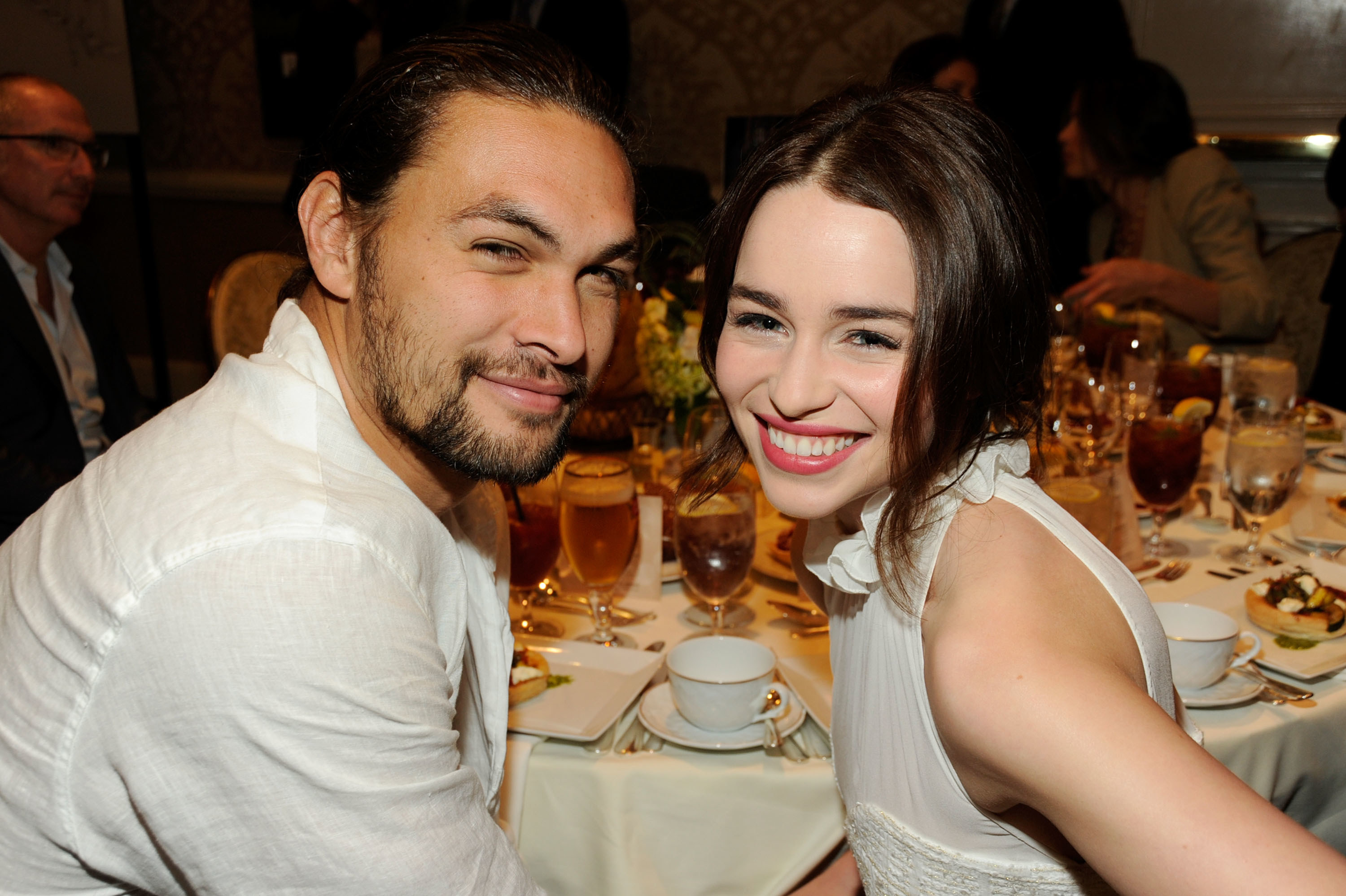 Jason and Emilia smile while sitting at a dinner table together