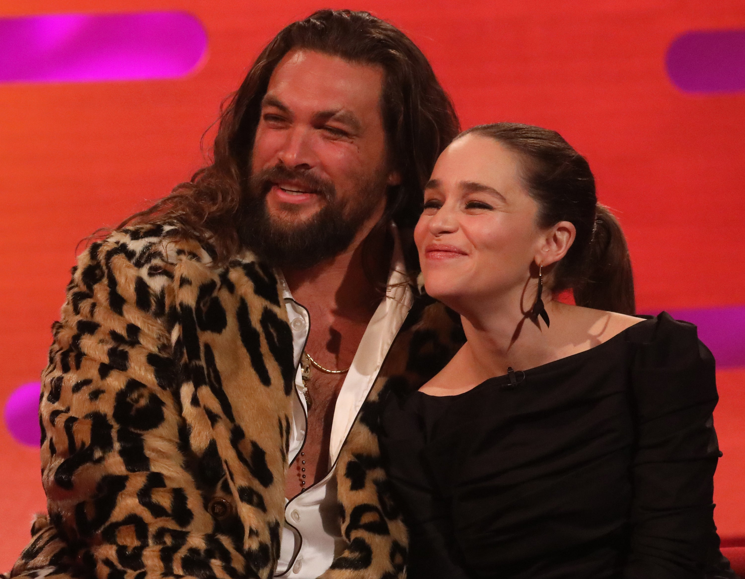 Jason wears a leopard jacket while sitting next to Emilia during a talk show interview
