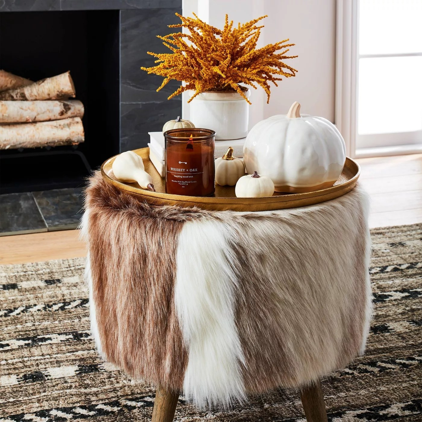 The faux fur ottoman functioning as a small table in a living room