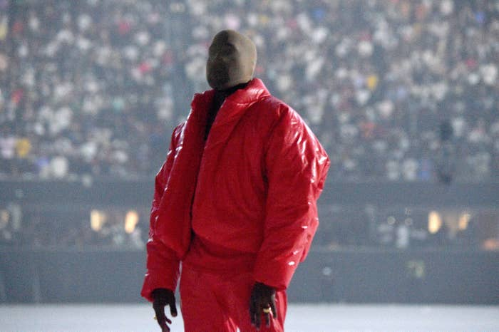 kanye west wearing a puffy red jacket and face mask