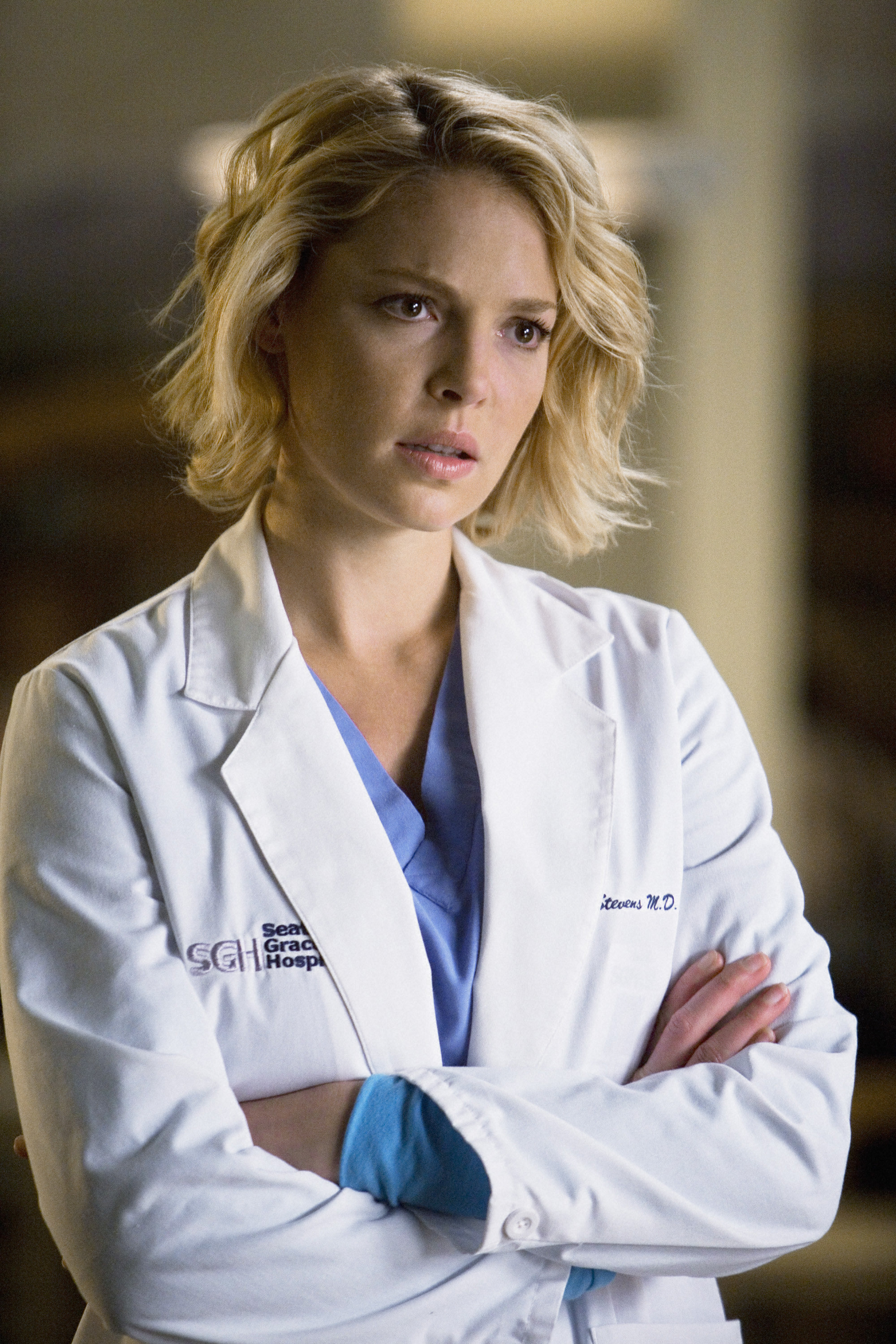 Heigl looks distressed with her arms crossed while wearing a doctor's coat