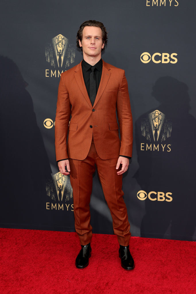 Jonathan Groff on the red carpet in a burnt orange suit