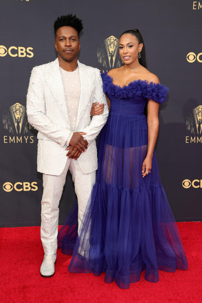 Leslie Odom Jr. wears a light colored fuzzy suit and Nicolette Robinson wears an over the shoulder gown