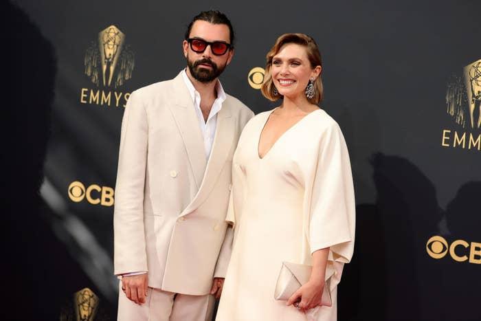Elizabeth Olsen wears a deep v-neck light colored gown and Robbie Arnett wears a light colored suit