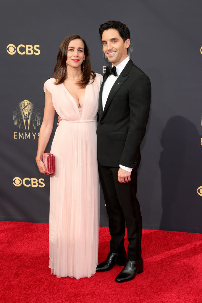 Paul W. Downs wears a dark suit and Lucia Aniello wears a sheer v-neck gown