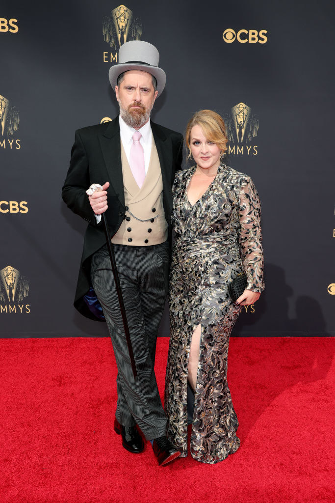 Brendan Hunt wears a dark suit, light colored vest, and a top hat, and Shannon Nelson wears a floral long sleeve gown with a slit up her thigh