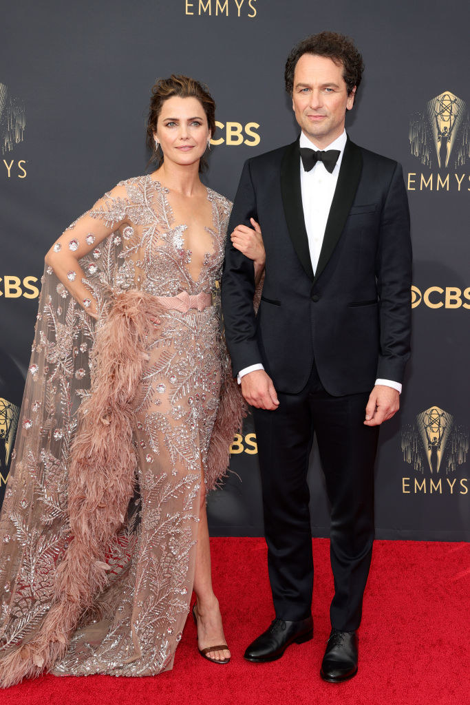 Keri Russell wears a crystal encrusted gown with a long train and Matthew Rhys wears a dark suit