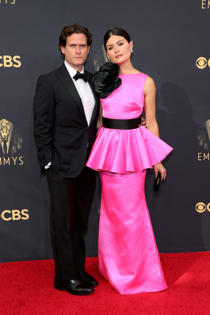 Phillipa Soo wears a brightly colored gown with a ruffle skirt around the middle and Steven Pasquale wears a dark suit