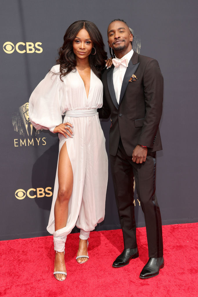 Zuri Hall wears a light colored jump suit and Scott Evans wears a dark suit