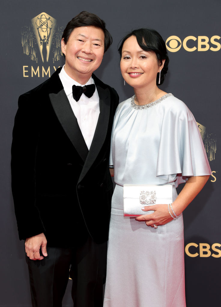 Ken Jeong wears a dark suit and Tran Jeong shiny gown with oversized short sleeves