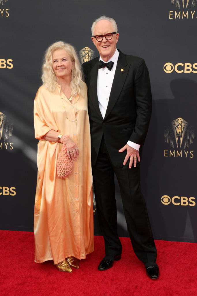 John Lithgow wears a dark suit and Mary Yeager wears a brightly colored floor length gown