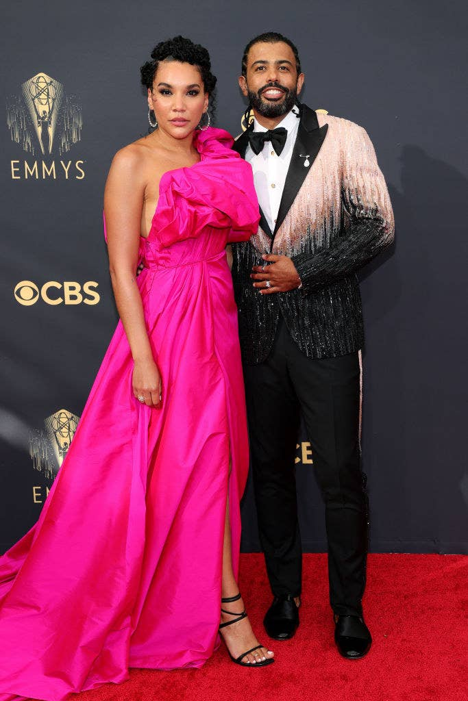 Emmy Raver-Lampman wears a one shoulder brightly colored gown and Daveed Diggs wears a dark suit