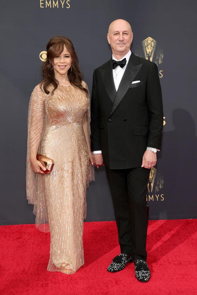 Rosie Perez wears a floor length and Eric Haze wears a dark suit