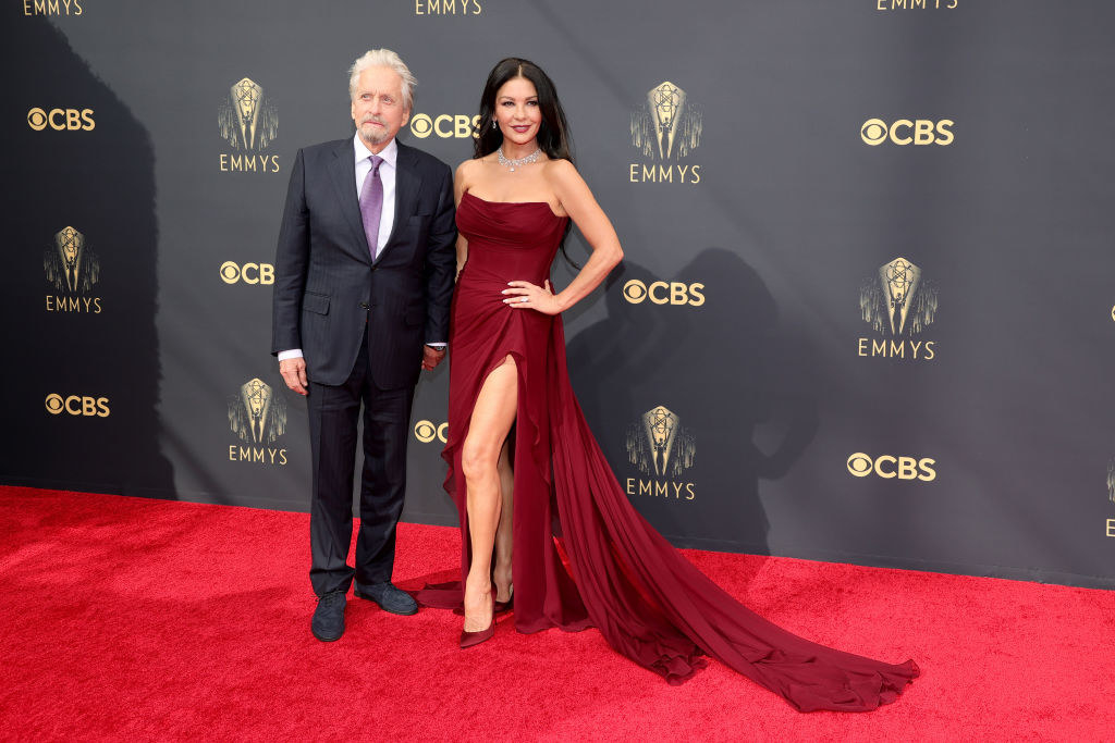 Michael Douglas wears a dark suit and Catherine Zeta-Jones wears a strapless dark colored gown with a long train