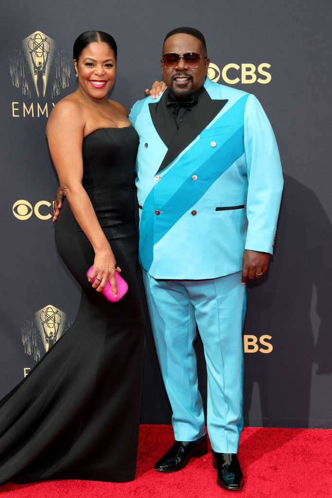 Cedric the Entertainer wears a brightly colored suit and Lorna Wells wears a strapless gown with a long train