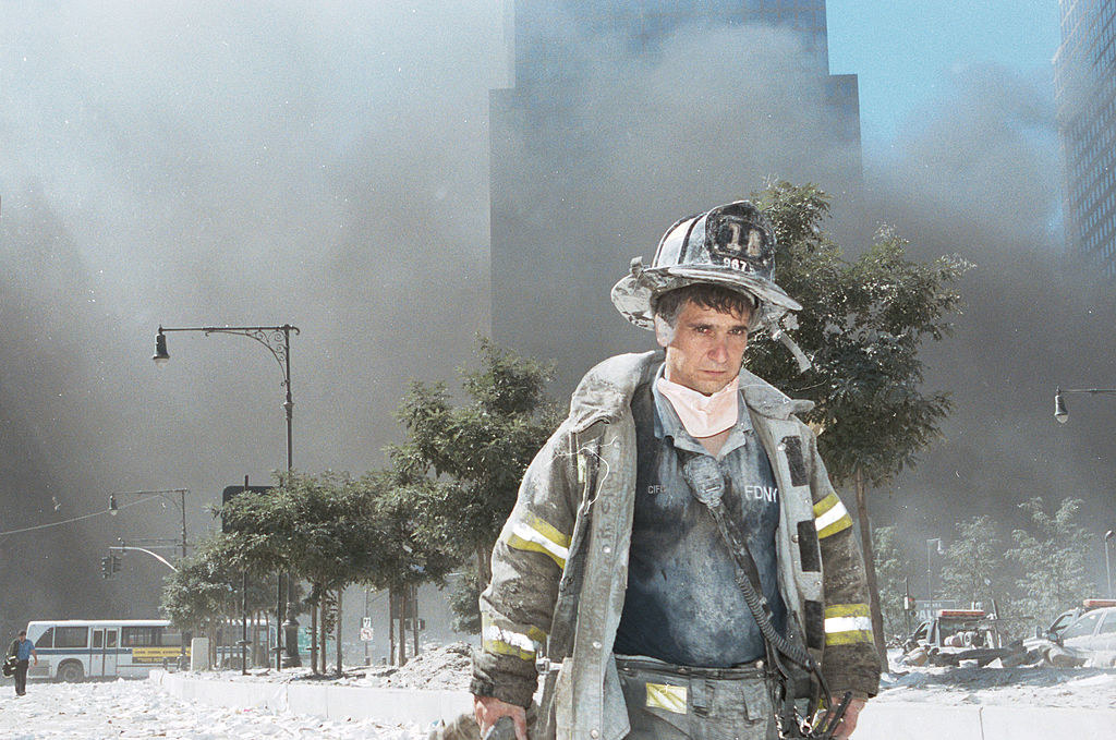 An unidentified New York City firefighter walks away from Ground Zero after the collapse of the Twin Towers September 11, 2001 in New York City