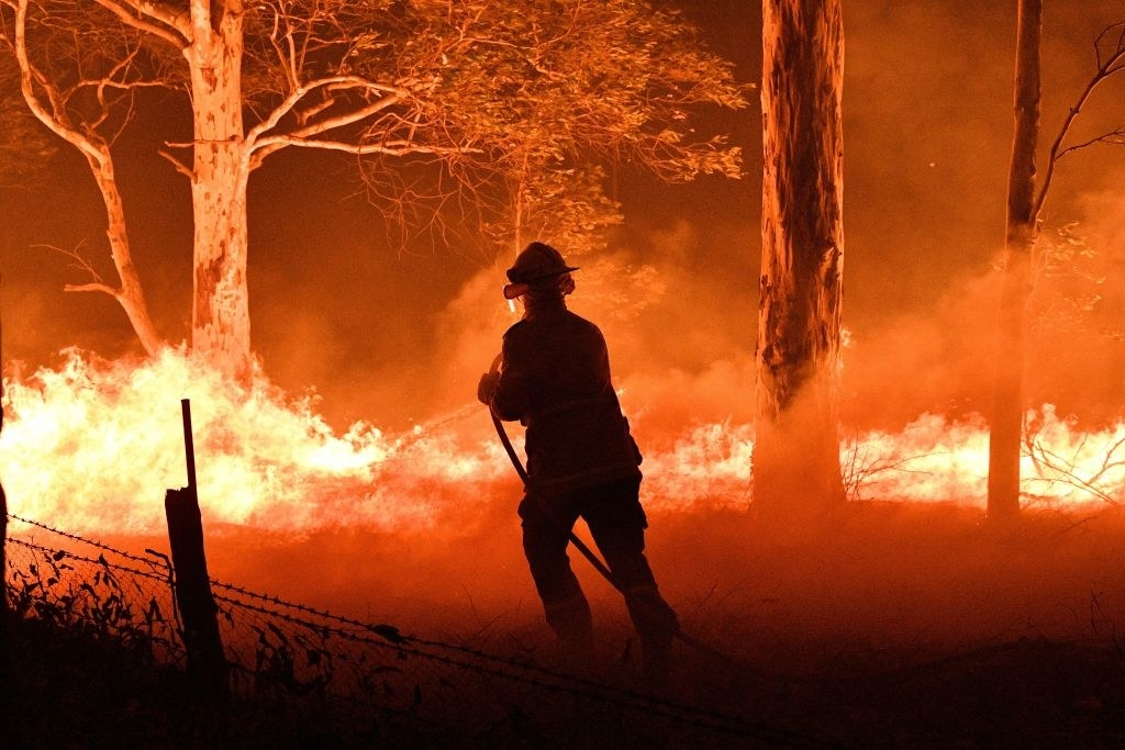 A firefighter hosing down trees and flying embers in an effort to secure nearby houses from bushfires near the town of Nowra in the Australian state of New South Wales