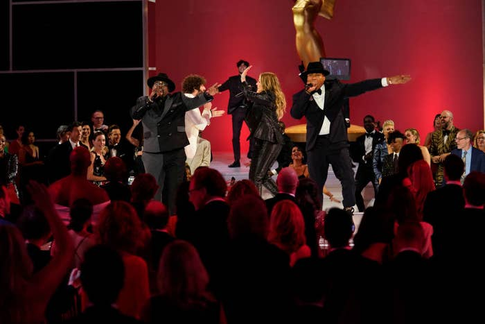 Host Cedric the Entertainer rapping onstage with others during the show's opening